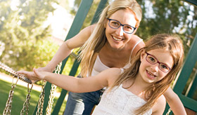 Mother and daughter wearing eyeglasses outdoors.