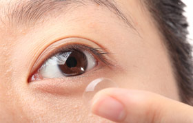 Woman applying contact lens to her eye.