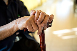 Seated elderly person grasping a cane.