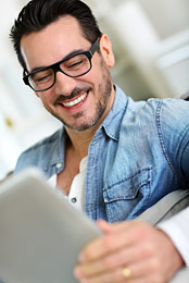 Man with eyeglasses looking at tablet device.