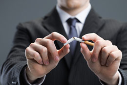 Man in business suit breaking a cigarette in half.