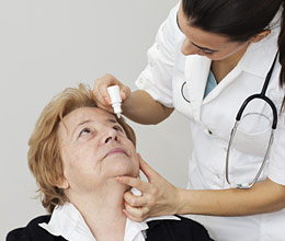 Woman receiving eye drops from health care provider