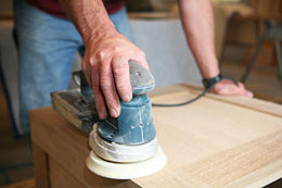 Man using a sander on a white oak cabinet.