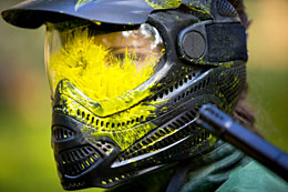 Girl wearing paintball helmet, covered with yellow paint.