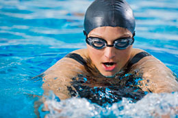 Woman swimming with contact lenses and swim goggles.