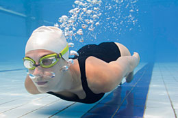 Woman swimming underwater with swim goggles.